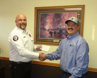 (L to R) Shad Cooper, Fire Chief and Fire Warden for Sublette County Unified Fire, accepts a donation of $800 from Josh Rose representing Enterprise Products.   Photo by Dawn Ballou, Pinedale Online!